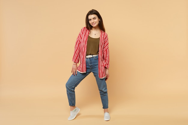 Portrait of beautiful smiling young woman in casual clothes standing looking camera isolated on pastel beige wall background in studio. people sincere emotions, lifestyle concept. mock up copy space.