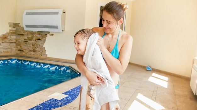 Portrait of beautiful smiling young woman covering and wiping her 3 years old little son after swimming in indoors pool