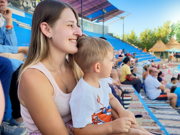Portrait of beautiful smiling young woman with her little son sitting on the arena tribunes and waiting for the show