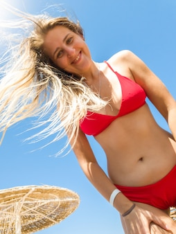 Portrait of beautiful smiling young woman with long hair wearing red bikini posing on the sea beach and looking in camera