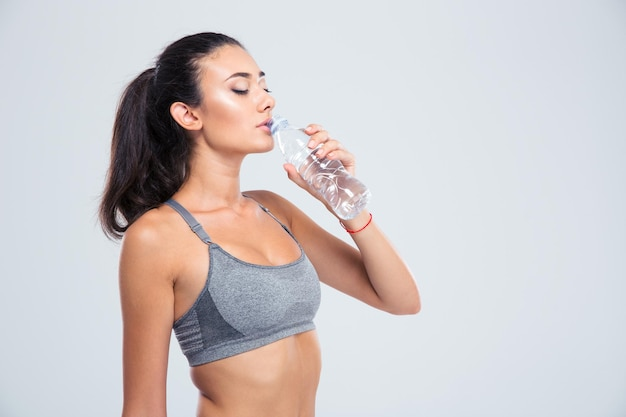 Portrait of a beautiful sports woman drinking water isolated on a white wall