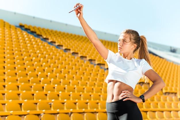 Portrait of a beautiful sports woman making selfie photo on smartphone at stadium