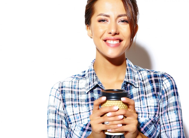 Portrait of beautiful stylish cool funny teenage woman going crazy in checkered shirt, holding plastic coffee cup