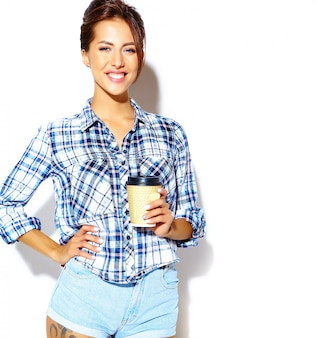 Portrait of beautiful stylish cool  teenage woman in checkered shirt, holding plastic coffee cup