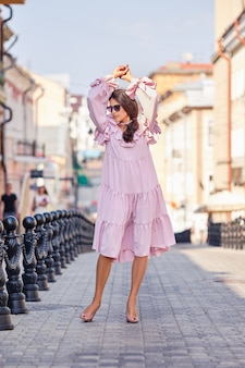 Portrait of beautiful stylish model in pink dress posing with hands up