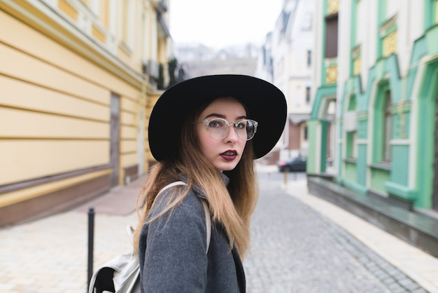 Portrait of a beautiful stylish woman in a hat and glasses on the background of the street of the old town.