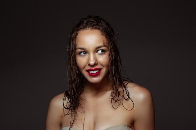 Portrait of beautiful stylish woman isolated on dark studio background