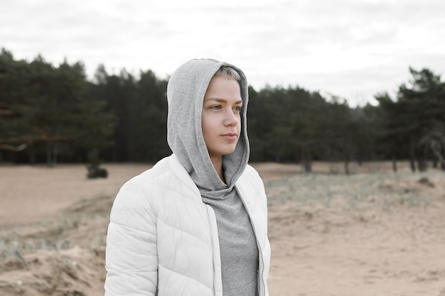 Ritratto di bella ed elegante giovane donna caucasica cappuccio e giacca bianca che hanno camminato sulla spiaggia di sabbia deserta durante le vacanze via mare. tempo libero, relax, attività, persone e concetto di stile di vita