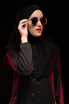 Portrait of beautiful stylish young muslim woman wearing black hijab and sunglasses as modern eastern fashion concept posing on black background