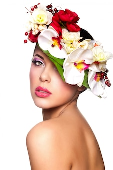Portrait of beautiful stylish young woman with colorful flowers on head