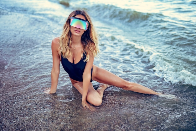 Portrait of beautiful sunbathed woman in mono sunglasses with long hair in swimsuit lying on summer beach