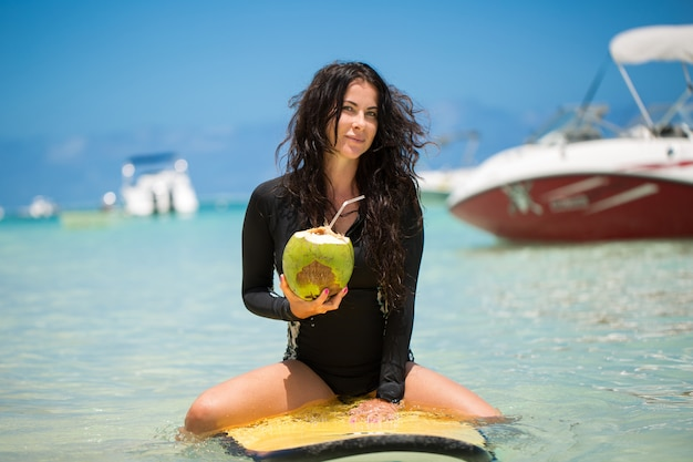 Portrait of a beautiful surfing girl with green coconut from palm tree sit on yellow surf longboard surfboard board