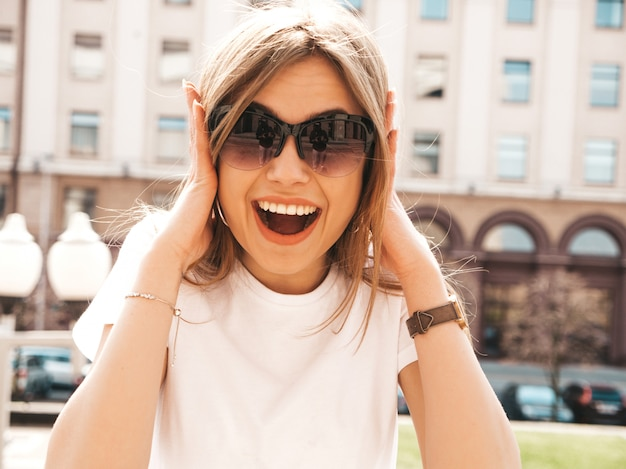 Portrait of beautiful surprised blond model dressed in summer hipster  clothes. trendy girl posing in the street background. funny and shocked woman