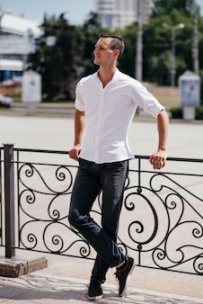 Portrait of a beautiful tall man in a white shirt on the street.