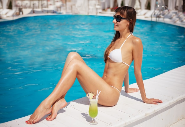 Portrait of beautiful tanned exotic woman relaxing near swimming pool in white swimwear with yellow cocktail. manicure and pedicure. hot summer day and bright sunny light.
