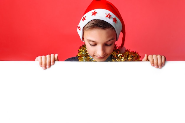 Portrait of a beautiful teen in santa's hat and with tinsel on her neck holding blank board