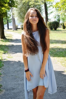 Portrait of beautiful teenage girl in blue blouse, against green of summer park play with her hair.