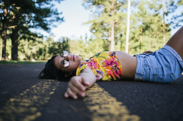 Portrait of a beautiful teenage girl lying on the pavement.