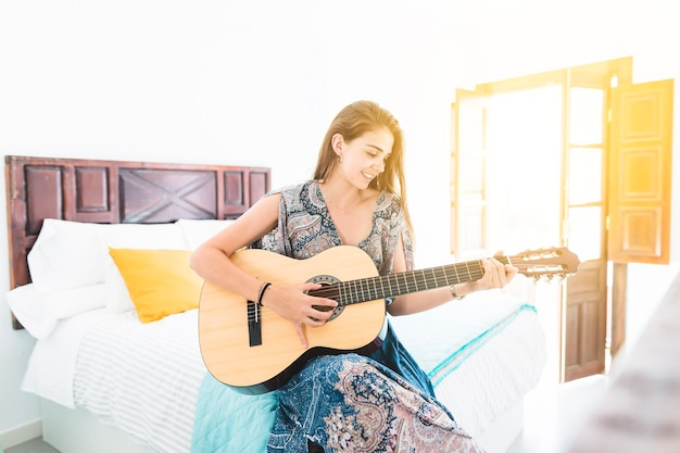 Portrait of beautiful teenage girl sitting on bed playing guitar