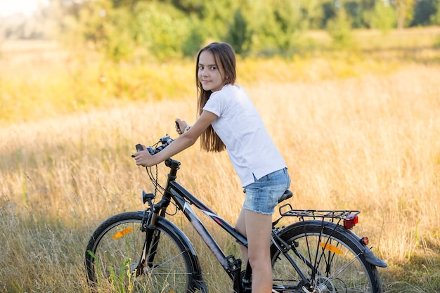 Portrait of beautiful teenage girl sitting on bicycle at meadow