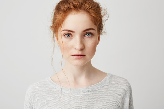 Portrait of beautiful tender ginger girl with blue eyes posing .