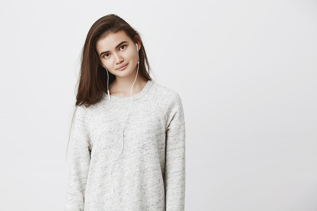Portrait of beautiful tender young adult woman, standing straight while smiling and wearing earphones. cute woman learns foreign language listening audio course she uploaded