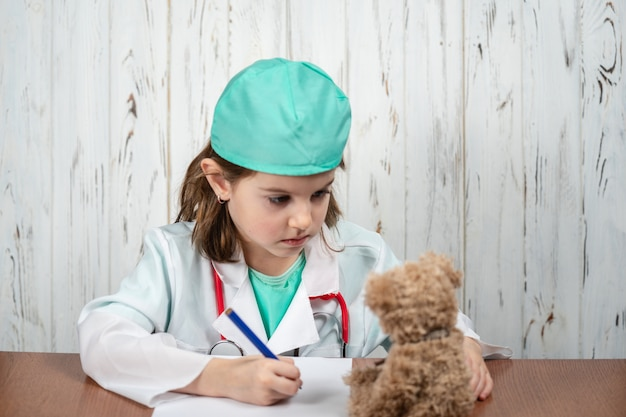 Portrait of beautiful thoughtful little girl role playing doctor, daydreaming and creating ideas in her mind. creative process. education and school concept. selective focus