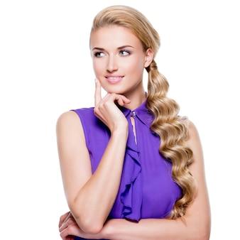 Ritratto di bella donna premurosa con capelli ricci biondi lunghi sul muro bianco.