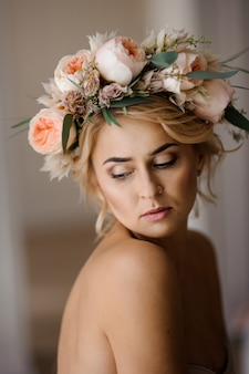 Portrait of the beautiful topless blonde woman in a floral wreath with closed eyes
