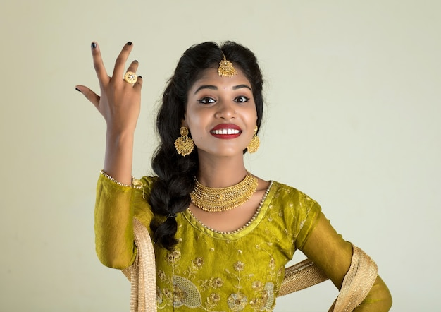 Portrait of beautiful traditional indian girl posing on white wall.