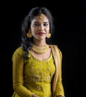 Portrait of beautiful traditional indian woman posing on black wall.