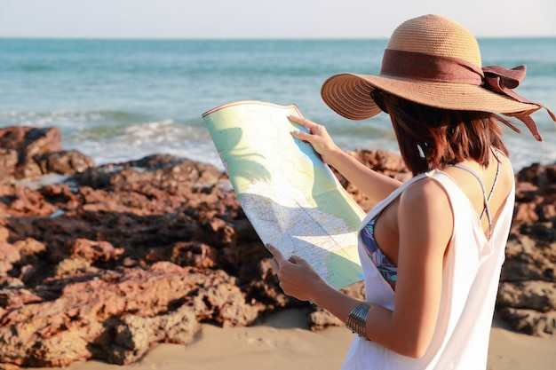Portrait of beautiful traveler woman looking and checking map on the island beach