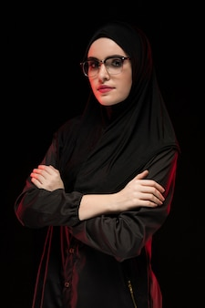 Portrait of beautiful trendy young muslim woman wearing black hijab and glasses as modern eastern fashion concept posing  black