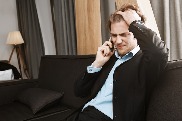 Portrait of beautiful unhappy bearded man with blonde hair talking on phone and being upset about finance problems in company.