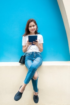 Portrait of beautiful university student is smiling on blue wall background