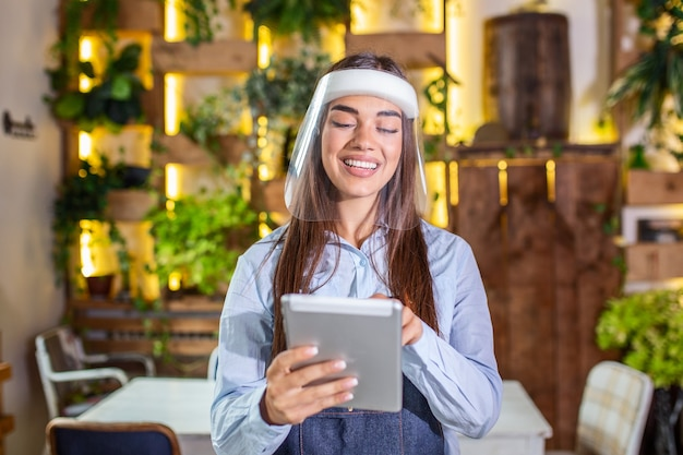Portrait of beautiful waitress wearing face shield while holding touchpad and looking at the camera in a pub or restaurant during covid-19 epidemic.