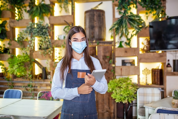 Portrait of beautiful waitress wearing protective face mask while holding touchpad and looking at the camera in a pub or restaurant during covid-19 epidemic.