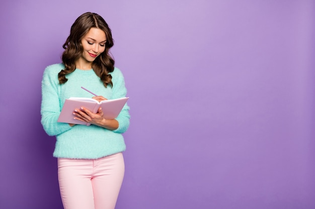 Portrait of beautiful wavy lady hold planner write essay responsible student writing main quotes famous writers wear pastel fuzzy sweater pink trousers.
