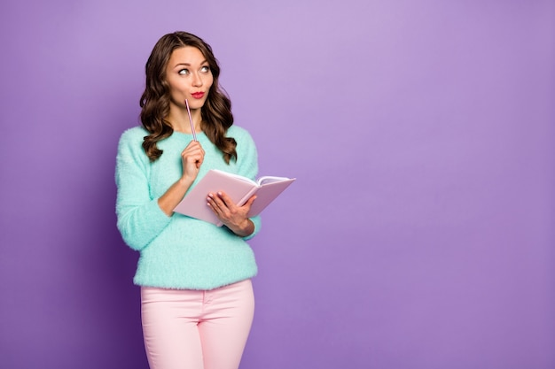 Portrait of beautiful wavy lady hold planner write own novel look empty space interested waiting inspiration wear fuzzy sweater pastel pink trousers.