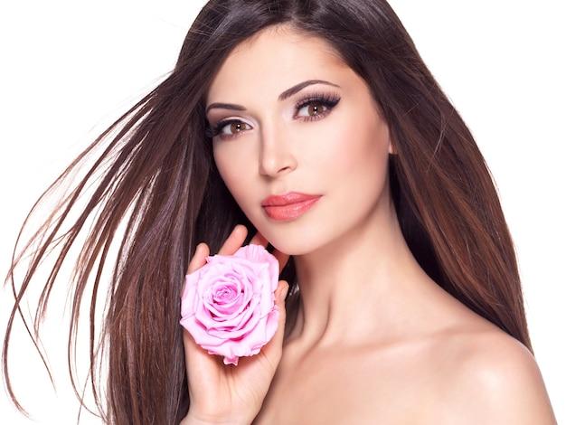 Ritratto di una bella donna graziosa bianca con lunghi capelli lisci e rosa rosa sul viso.