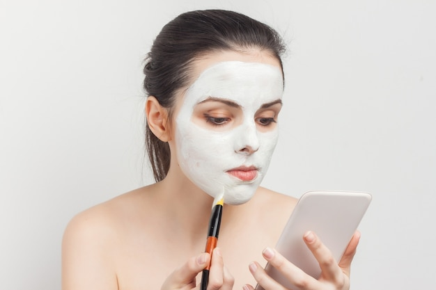 Portrait beautiful woman applying a face mask with a brush mirror clear skin
