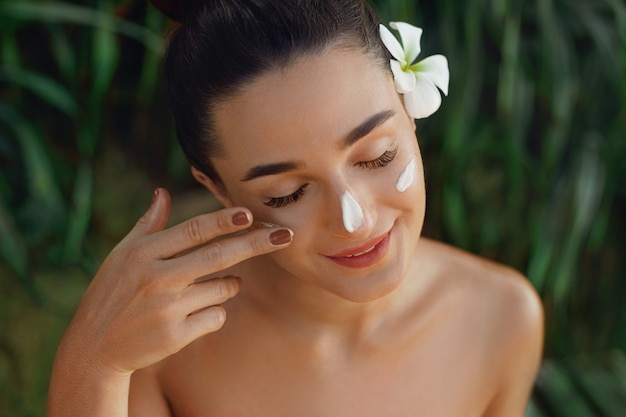Portrait of beautiful woman applying sun cream