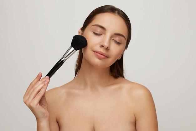 Ritratto di una bella donna come applicare il trucco vicino a uno specchio