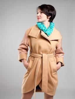 Ritratto di bella donna in cappotto beige di autunno con la sciarpa verde