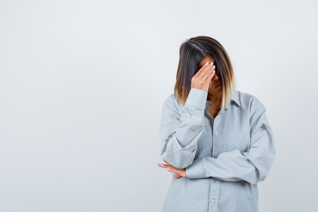 Portrait of beautiful woman bending head down in shirt and looking sorrowful front view