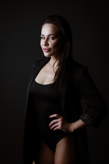 Portrait of a beautiful woman in a black bodysuit and jacket posing on a dark background