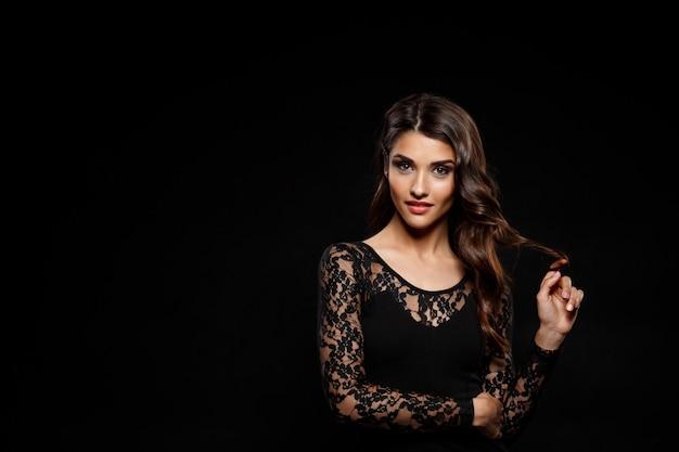 Portrait of beautiful woman in black dress over dark wall