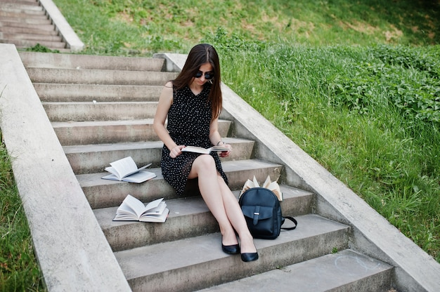 Portrait of a beautiful woman in black polka dot dress and sunglasses sitting on the stairs with books and backpack in the park.