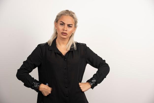 Ritratto di bella donna in camicia nera in posa su sfondo bianco. foto di alta qualità