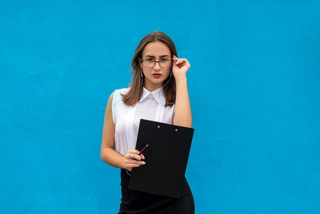 Portrait of beautiful woman in business clothes with clipboard writing, isolated on blue